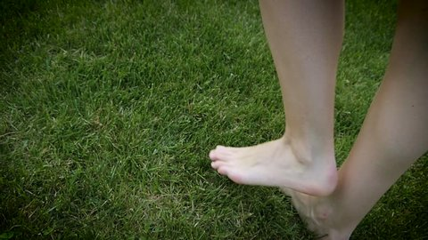 Barefoot woman legs walking on a green grass lawn on backyard in slow motion