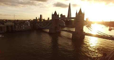 Aerial view of the iconic landmark Tower Bridge in London during the golden hour sunset. London's tallest building - the Shard, is seen in the background.