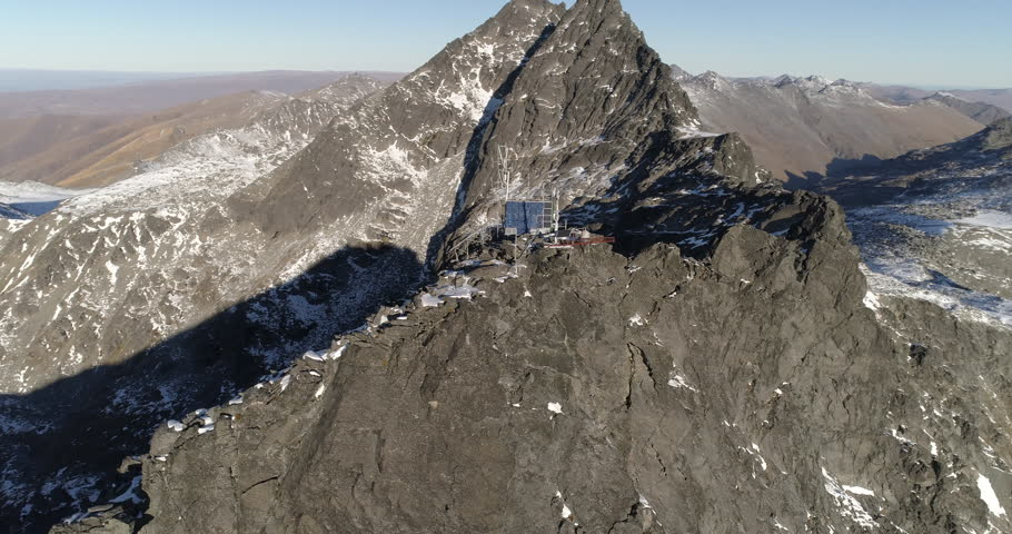 Aerial footage pan around hut on snow capped mountain summit. New Zealand in Autumn before sunset. 4K