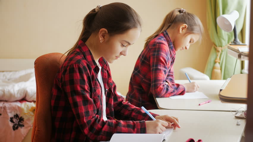 4k footage of two sisters writing in notebooks with pens behind desk at bedroom | Shutterstock HD Video #27329860