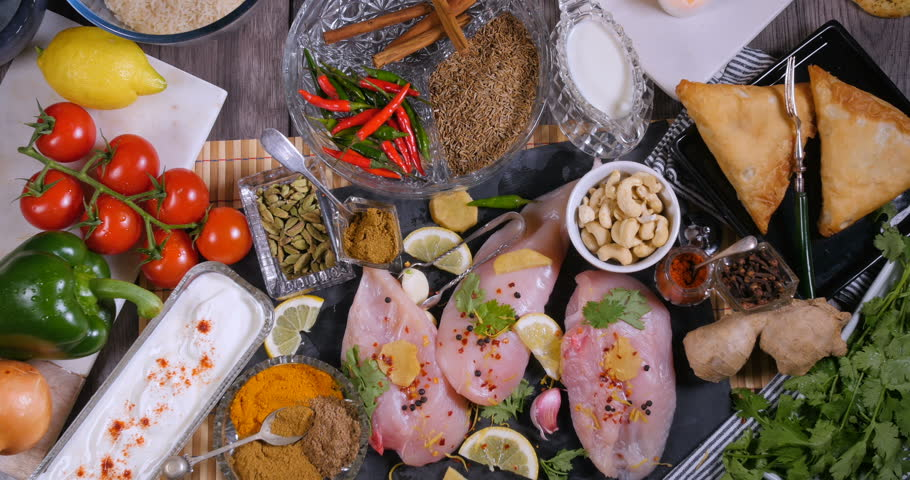 Top down zoom out view of ingredients and indian spices for chicken tikka masala