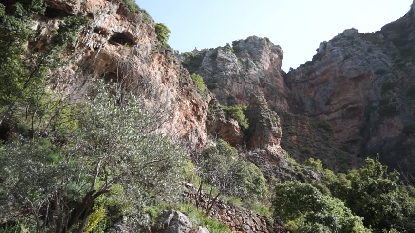Qadisha Valley. Pan-left shot of cave entrances on a rock face in Qannubin. Caves of the valley have been used for habitation since Paleolithic time.