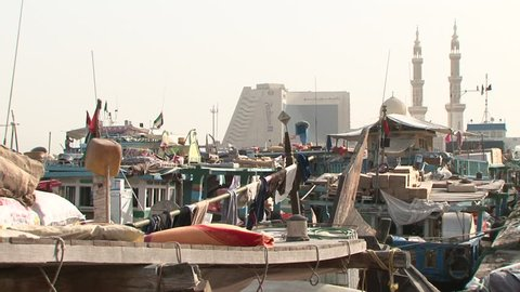 DUBAI, UAE - CIRCA 2008: Static shot of dhows wharfed at Deira harbour with Radisson Blu hotel in the background. Dhow wharfage is listed as a tourist attraction in the UAE.