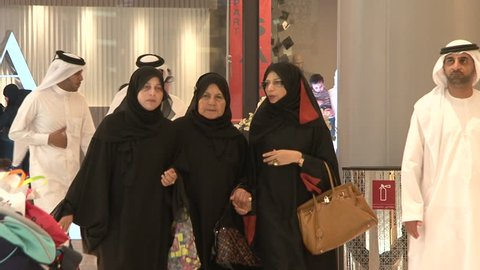UAE - CIRCA 2008: Pan-right shot of three veiled Emirati women of different ages walking in a mall.