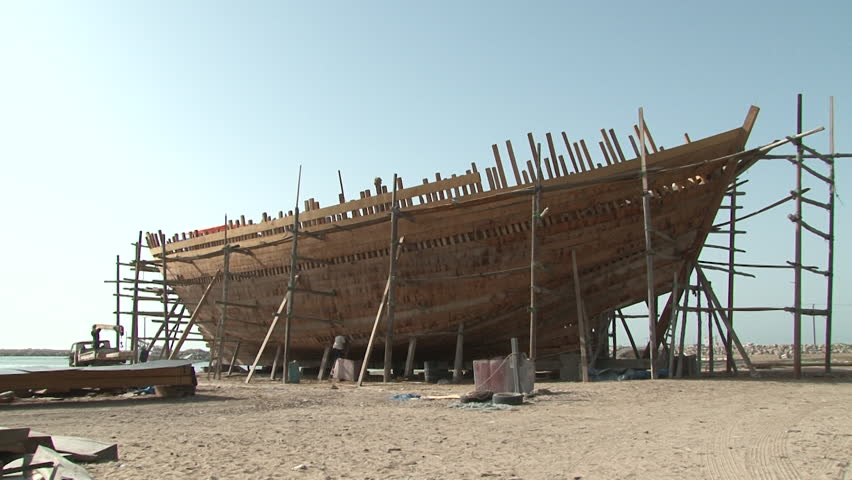 UAE - CIRCA 2008: Static shot of man in traditional Emirati dress at a boat construction on the seashore.