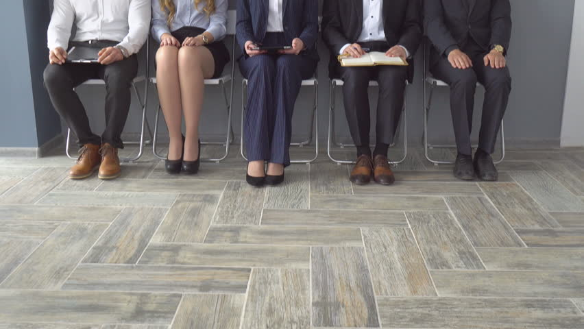 Unemployed expect interviews sitting on chairs in the hallway of an office building. | Shutterstock HD Video #27374050