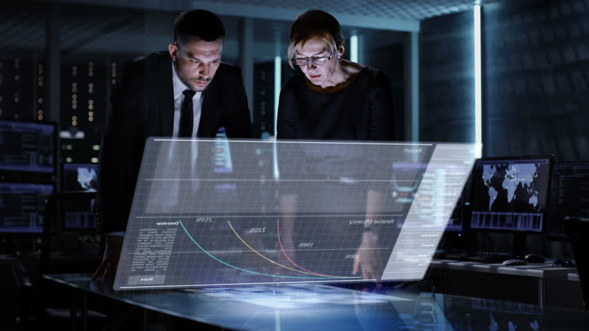 Male and Female Business Managers Use Touchscreen Interactive 3D Panel in Big Monitoring Room Full of Computers with Animated Screens.