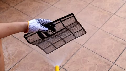 Person spraying water onto air conditioner filter to wash away thick dirty dust