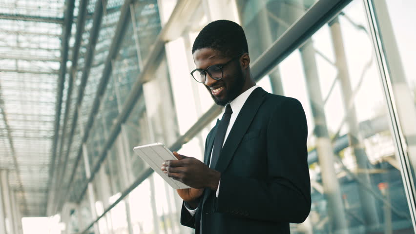 Happy african american businessman using tablet device while standing near big office windows outdoors. Man scrolling pages, tapping on touchscreen, checking financial charts. close up | Shutterstock HD Video #27449302