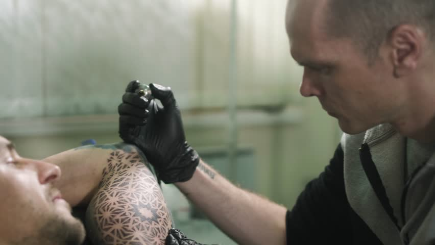The master does the tattoo of the man on his arm #27455560
