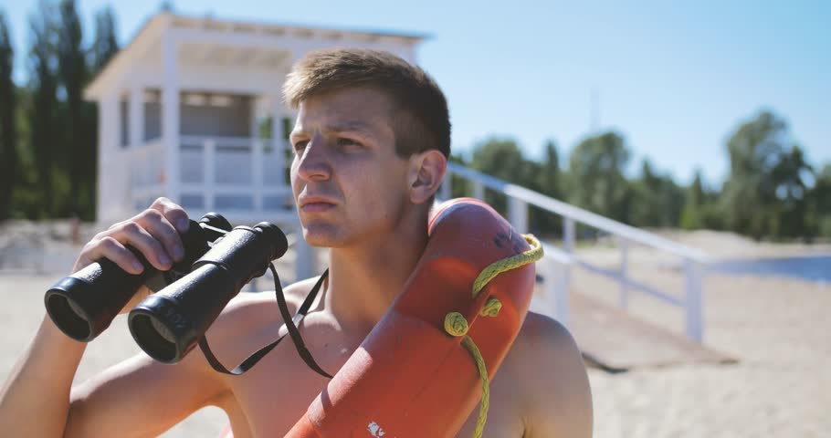 A beach lifeguard with a bare torso looks through binoculars watching suspicious personalities.