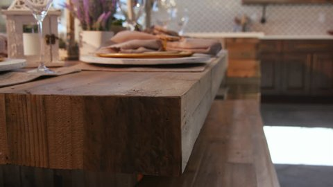 Dining Room Table Setting Detail Corner. view rises and lowers on a rustic modern wood dining room table setting. Plates, napkins, glasses and centerpieces