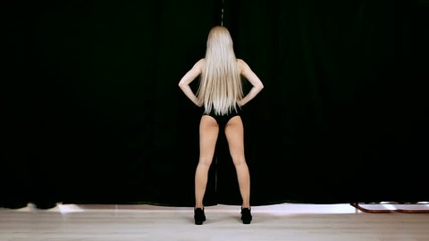 Young sexy blond woman 20-25 with very long flowing hair dances go-go on a black background. Static camera