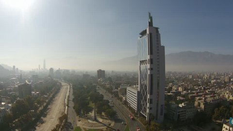 February, 2017 Santiago, Chile.Bird's eye tracking shot of busy street and Movistar building against smoggy Andes mountains