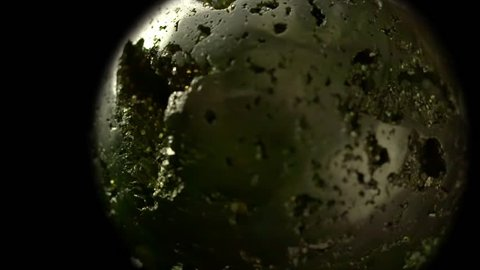 Spinning Golden Pyrite Globe - A ball of smoothed pyrite (fool's gold) spins in front of black, looking like an alien planet in the night sky, or suggesting that wealth makes the world go round.