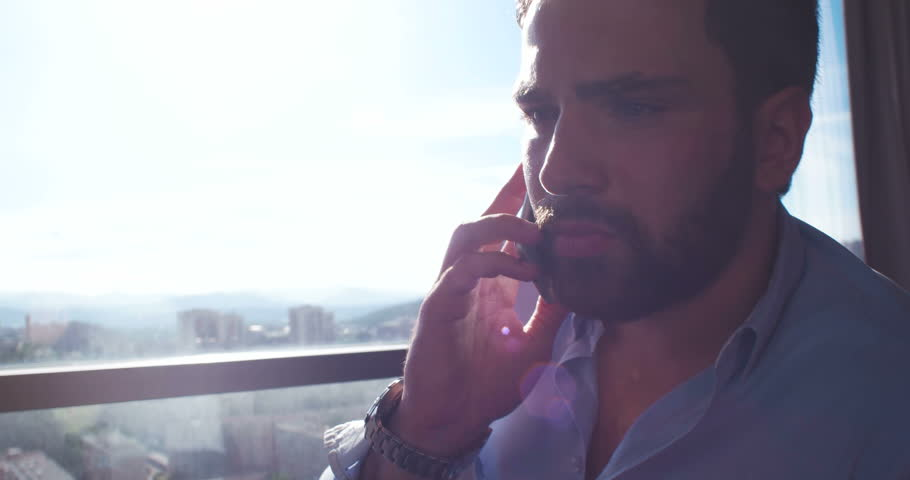 Business Man Talking On Cell Phone At Home with sun flares coming from window | Shutterstock HD Video #27548104