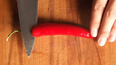 cutting red hot pepper on cutting board. professional chef's hand using knife to slice, chop chilli pepper for cooking. chili pepper being diced on wooden board top view. Healthy food. Close-up