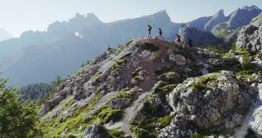 Aerial flight above people hiking along trail path in sunny day. Group of friends summer adventure journey in mountain nature outdoors. Travel exploring Alps, Dolomites, Italy. 4k drone forward video #27553420