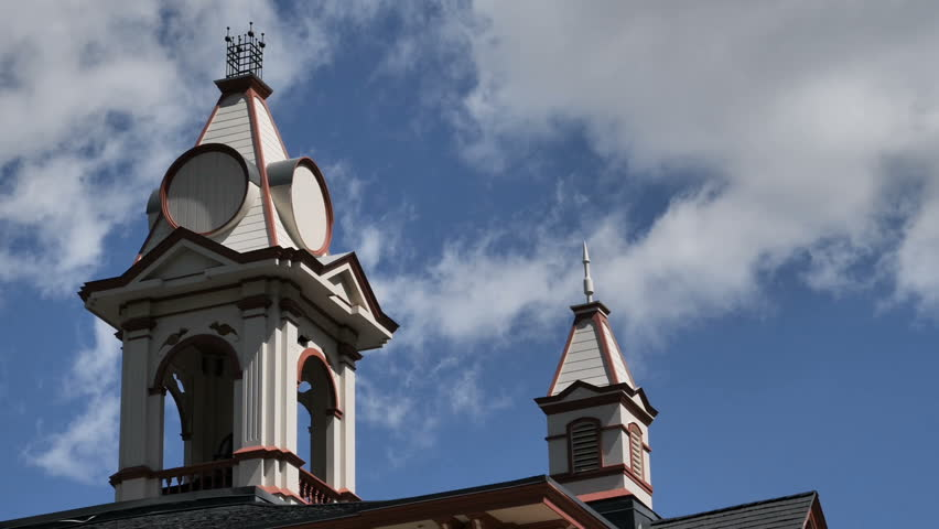 Time Lapse-White clouds against a blue sky blow past old circa 1874 school bell tower lighted by morning light
