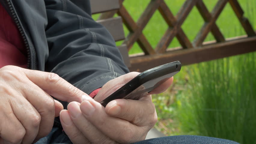 Elderly Man Sitting On Park Bench And Messaging On Mobile Phone | Shutterstock HD Video #27590311