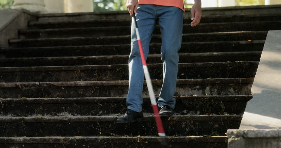 Hispanic blind man, latino people with disability, handicapped person and everyday life. Visually impaired man with walking stick, descending steps in city park