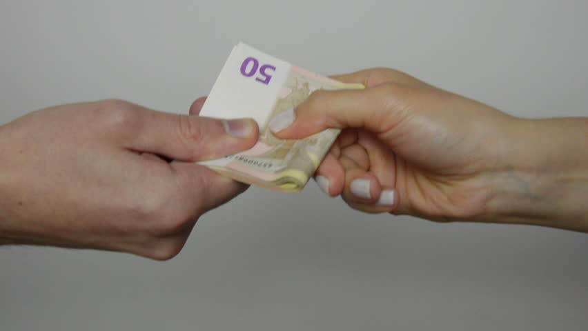 Hard Parting with Money. In the picture there is a man hand with a bundle of money and a woman hand. After a brief tug a woman hand wins. Euro cash. Close up of people hand. Static tripod shot.