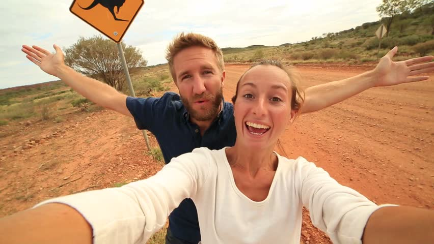 Cheerful young couple take a selfie portrait on the road standing next to a kangaroo warning sign in the Australian outback