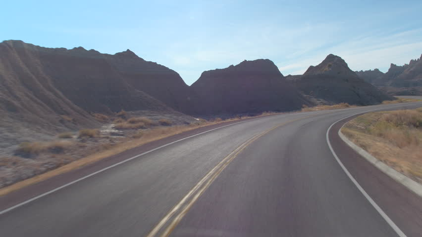 FPV: Driving along the empty road snaking through picturesque Badlands landscape with rocky sandstone formations. Traveling across the Badlands desert in South Dakota. Road trip across United States.