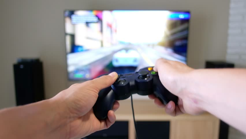 Gamepad in the player's hands opposite the large flat screen