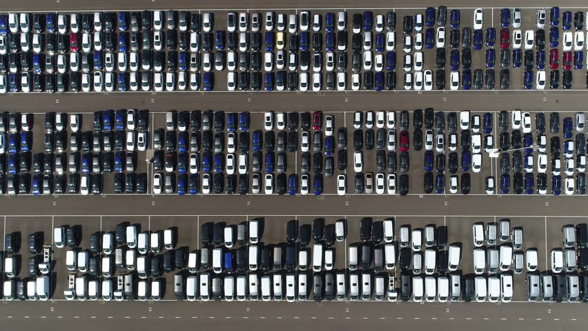 Aerial top down view flying to right over new car storage parking lot showing imported new vehicles or ready to export new automobiles storage facility car industry for American and European market 4k