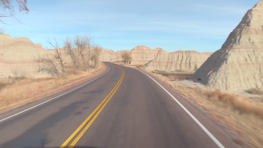 FPV: Driving along the empty road winding past amazing Badlands landscape with rocky sandstone mountains. Traveling across the Badlands grassland desert in South Dakota. Road trip across United States