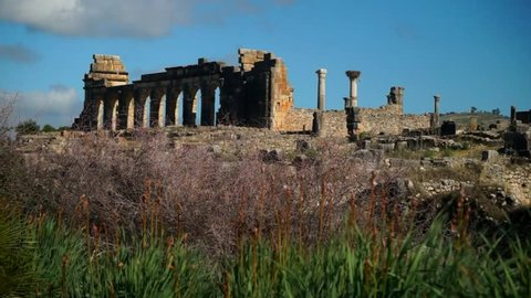 Wide, slider shot of ancient Roman ruins at the archaelogical UNESCO Heritage site of Volubilis in Morocco.