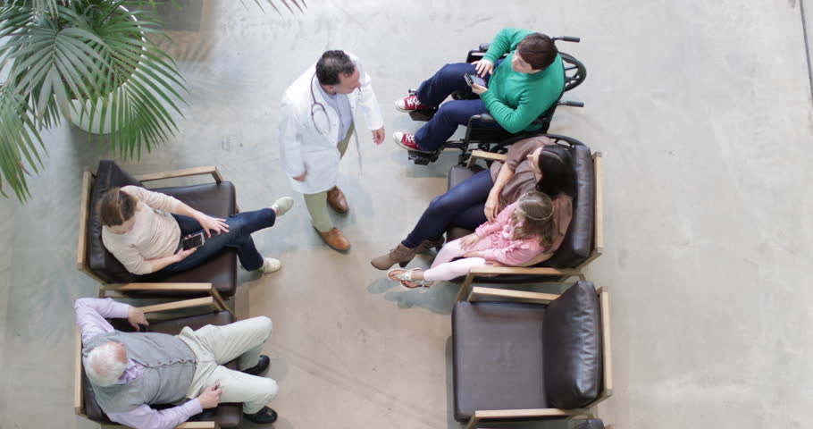 Overhead shot of Medical Doctor greeting Mother and Daughter in waiting room