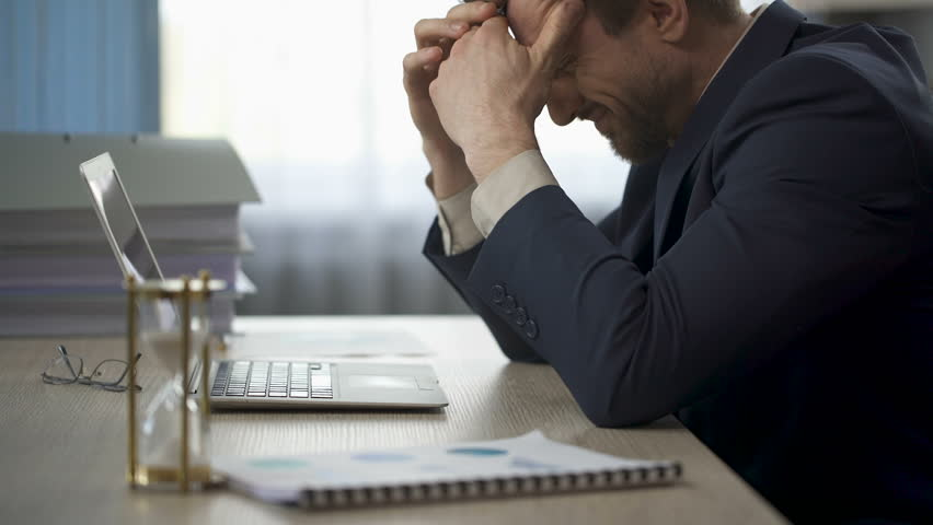 Man sitting at office desk with face in pain, head falling onto table, fatigue