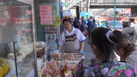 NEW YORK CITY, USA - MAY 17, 2017: Unidentified woman sells street food, Flushing Chinatown, Queens. Flushing has a large and growing Asian community.