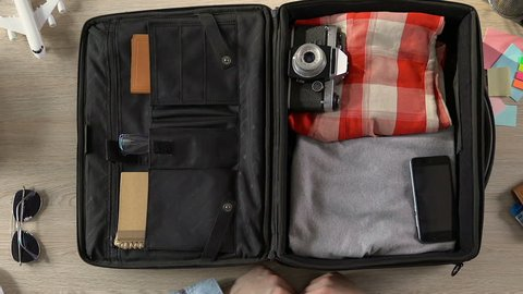 Traveler packing his suitcase, putting purse, passport with tickets and money