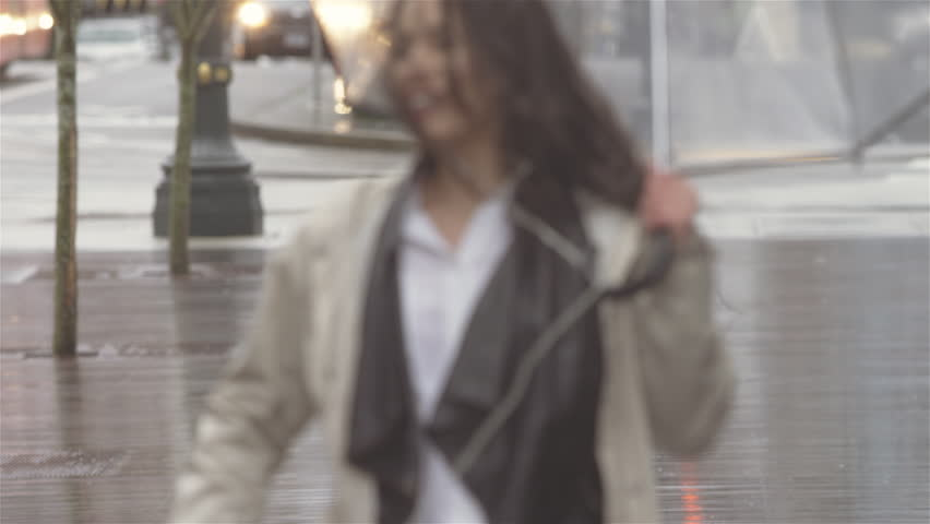 Young beautiful Latin woman dancing around with an umbrella in the city while listening to music. She then walks out of frame