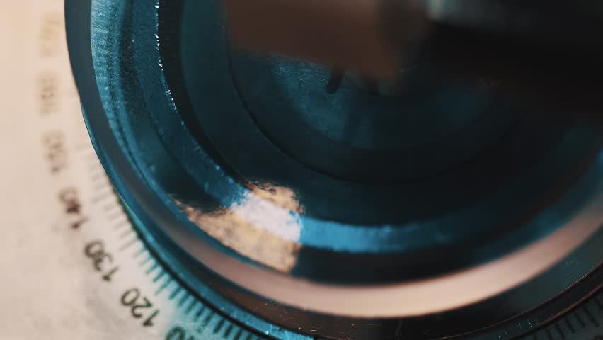 Blue glass lens fastened in fluid sealant machine with encrypted numbers disc at production facility, close up | Shutterstock HD Video #27727720