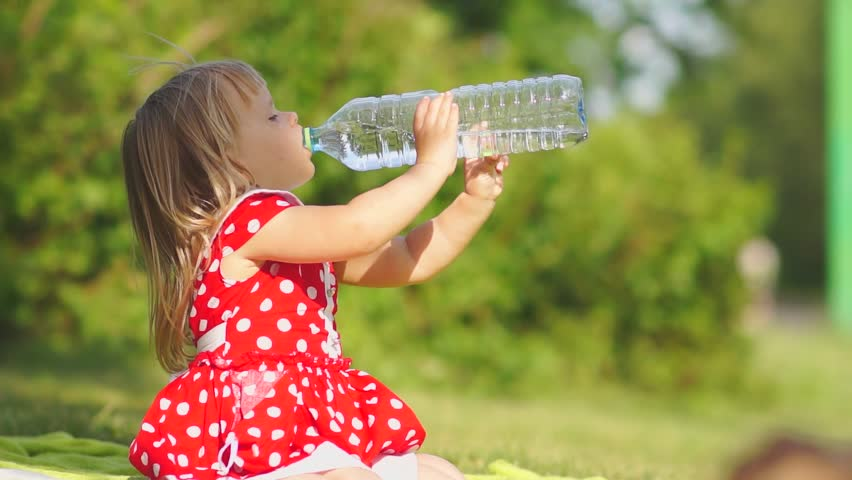 Adorable girl in beautiful dress drink water from large bottle