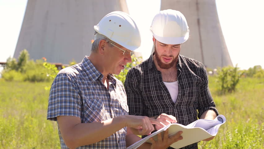 Two serious men engineers working with blueprints in an open industrial site. | Shutterstock HD Video #27734860