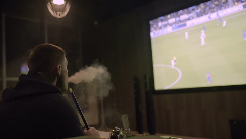 Man watching football on the big screen and smoking hookah