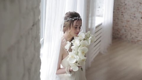 bc04a288eed Wedding day of bride in bridal gown. Beauty woman and bouquet. Fashion  brunette model indoors. Beauty portrait of model in white bridal dress