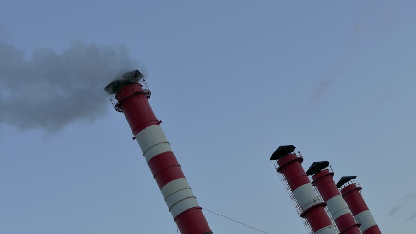 Smoke stack. Smoke comes from red-white chimneys on thermoelectric plant against sky. (av34323c)