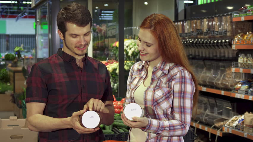 Attractive young couple arguing about the food composition data at the hypermarket. Handsome brunette man and his pretty redhead girlfriend pointing their forefingers on the can with some product