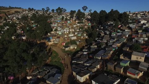 An aerial view of a township early one morning in Cape Town showing colourful zinc houses on a hill and african people heading off to work.