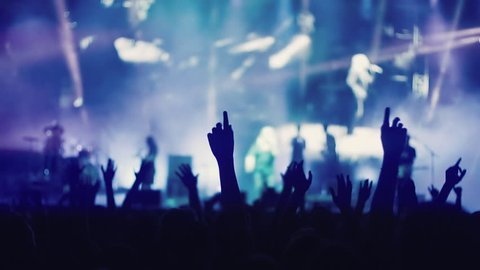 Iconic night rock concert front row crowd cheering hands in air slomo 100p.An outdoor summer night rock concert.People cheer move lift and clap their hands in unison against the strobing stage lights.