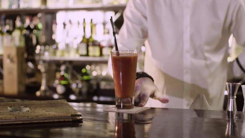 The barman in white shirt moves the finished bloody Mary to the edge of the bar counter close-up slow motion.