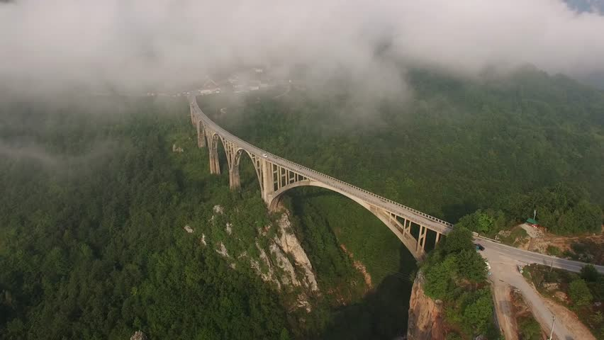 Morning fog clouds. Tara river canyon. Best of Montenegro beautiful nature Europe sightseeing's. Concrete arch bridge car road. Summer. Cinematic Aerial drone flight around 4k footage.