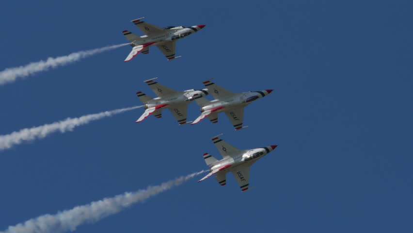 TITUSVILLE, FLORIDA - CIRCA MARCH 2017: USAF Thunderbirds Demonstration Team performs at airshow - four jets flying in tight formation rolling over with smoke trails in super slow motion