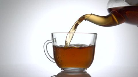 Tea pouring. Tea being poured into glass transparent tea cup. Teapot and teacup. Tea time. Slow motion 240 fps. 4K UHD video 3840X2160